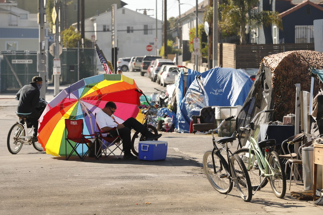 Richard Thompson seeks the shade of his umbrella as he is camped out with several others in a Venice parking lot across the street from one of 20 homeless shelters that have been established by Mayor Garcetti.(Al Seib/Los Angeles Times)