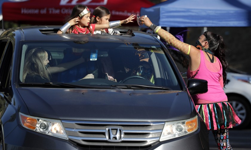 Jennifer Olivas hands treats to 6-year-old twins Loucia Ramirez, left, and Adriana Ramirez during the Monterey Park Candy Caravan on Oct. 29, 2020. (Myung J. Chun / Los Angeles Times)