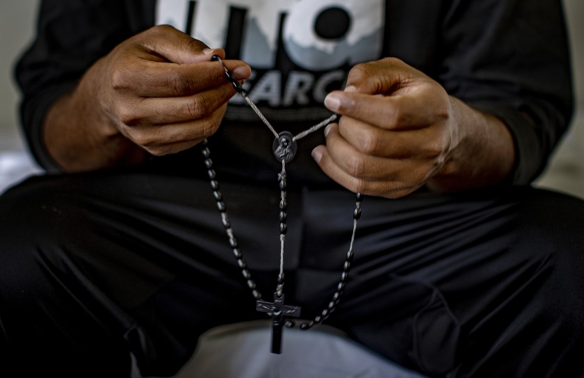 Tsegai, who fled persecution in Eritrea, holds a rosary given to him by family members. After he was released from the Adelanto ICE Processing Facility on Sept. 8, 2020, an Episcopal church in San Bernardino County took him in. Shut down by the COVID-19 pandemic, some churches are housing immigrants released from detention. (Gina Ferazzi / Los Angeles Times)