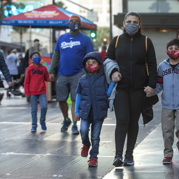 From left, Daniel Garcia, 5, his mother, Magdalena Hernandez, 40, and brother Alonso Garcia, 9, from Commerce, wear protective masks while walking along Hollywood Boulevard on Nov. 9, 2020. (Mel Melcon / Los Angeles Times)
