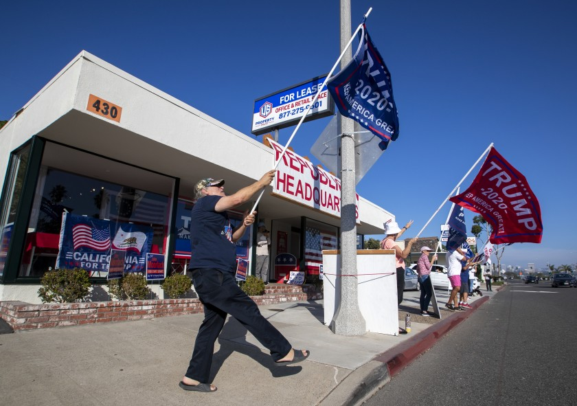 Trump supporters shout to passing motorists in front of GOP headquarters on Nov. 3, 2020 in Newport Beach. (Allen J. Schaben/Los Angeles Times)