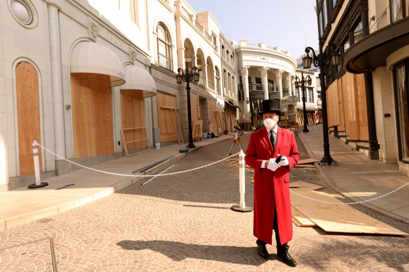 "Gregg Donovan former ambassador of Beverly Hills, stands on a closed and boarded-up Rodeo Drive on Nov. 2, 2020. ""I never thought I would see this,"" he said about businesses being closed along the famous street. (Los Angeles Times)"