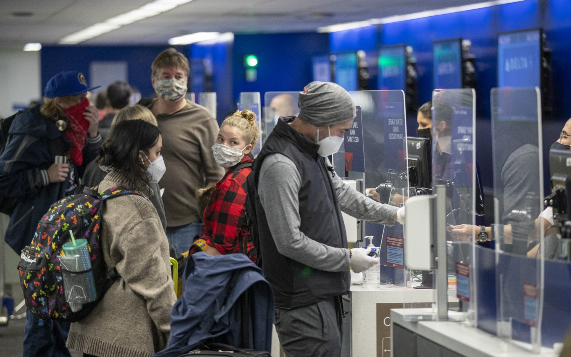 People wearing masks check in at Los Angeles International Airport as Thanksgiving holiday travel gets underway. Despite the public health warnings to avoid Thanksgiving plane travel, some people are taking the risk.(Allen J. Schaben / Los Angeles Times)