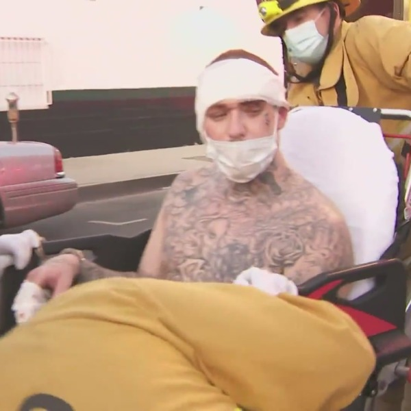 A man who barricaded himself in a Sherman Oaks home following a pursuit on the 101 Freeway in loaded into an ambulance after surrendering to authorities on Nov. 16, 2020. (KTLA)