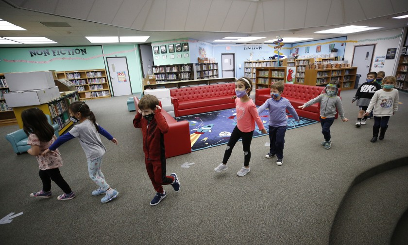 Kindergarteners at Lupin Hill Elementary School in Calabasas practice social distance walking through the library on Nov. 9, 2020. (Al Seib / Los Angeles Times)