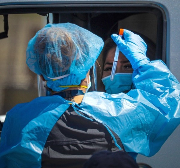 A San Bernardino County health care worker collects a sample at a drive-through coronavirus testing site in Victorville in 2020. (Irfan Khan / Los Angeles Times)