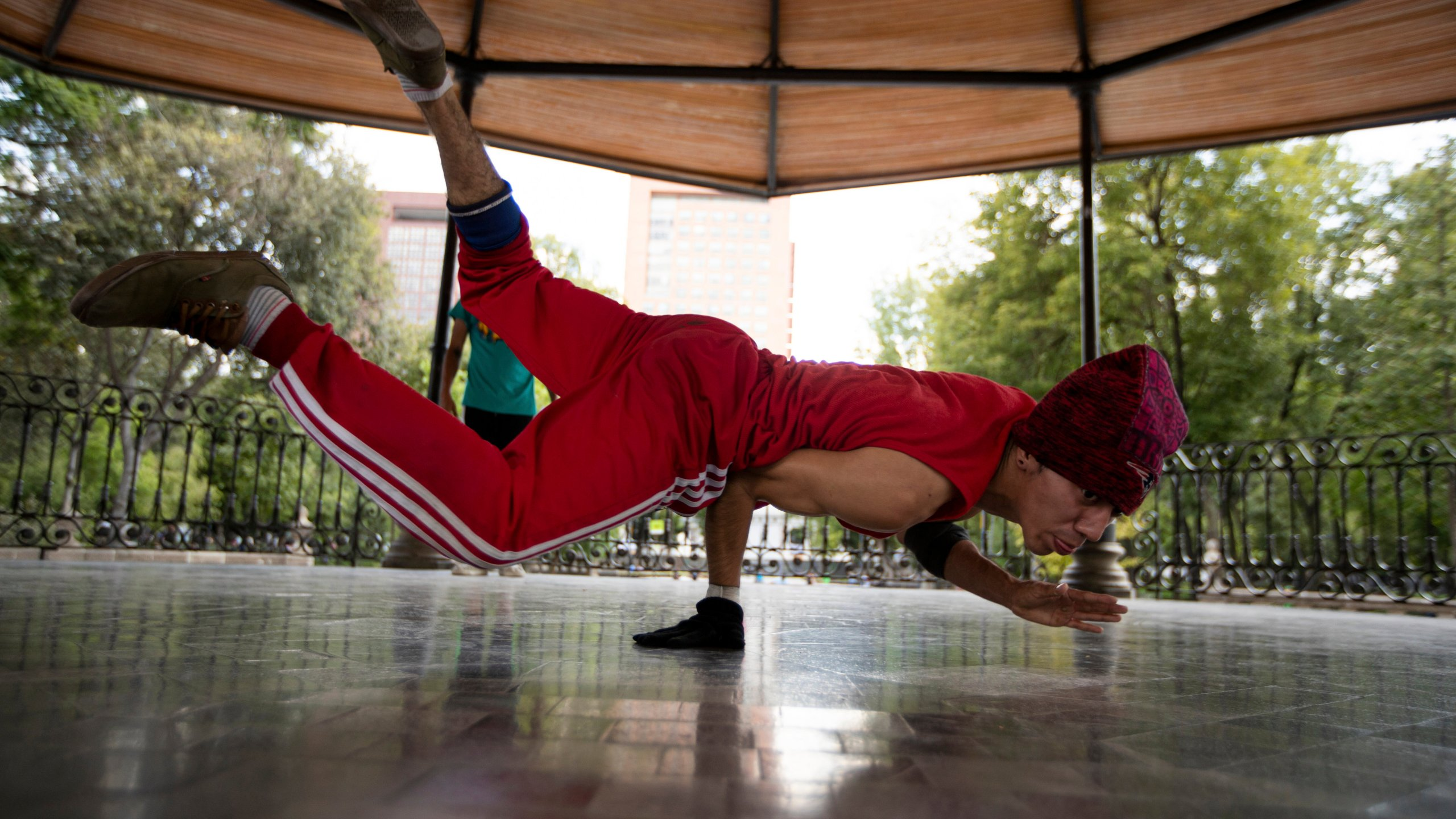 Carlos Cruz, a breakdancer, practices at a kiosk in Alameda park after being closed off to the public for nearly five months due to the new coronavirus pandemic, in Mexico City, Tuesday, Aug. 18, 2020. (AP Photo/Fernando Llano)