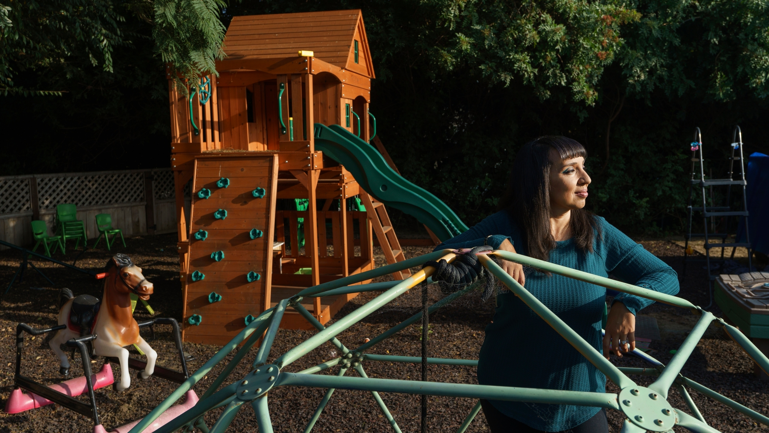 Mary De La Rosa stands inside a play structure in her home backyard, that once housed the now-closed child care program, Creative Explorers, Wednesday, Oct. 21, 2020, in Los Angeles. When De La Rosa closed her toddler and preschool program in March because of the coronavirus pandemic, she fully expected to serve the children again some day. In the end, though, Creative Explorers closed for good. The story of De La Rosa's program is being repeated across the country as the pandemic's effects ripple through child care, disproportionately affecting Black and Latino-owned centers in an industry that has long relied on providers of color. (AP Photo/Damian Dovarganes)