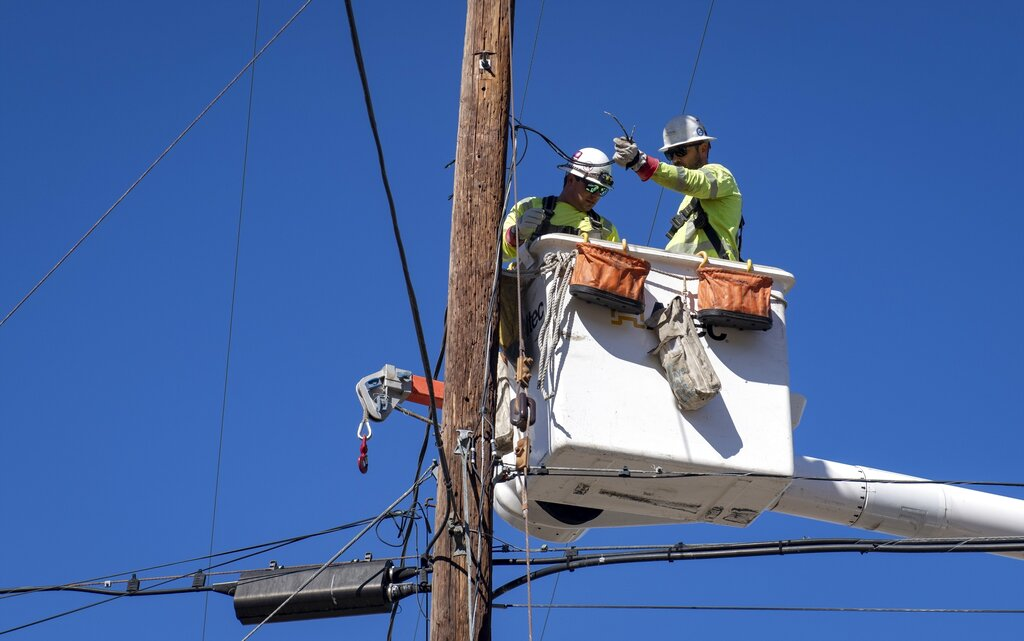 In this Oct. 25, 2019, file photo, Southern California Edison crews replace power lines in Santa Clarita. (AP Photo/ Christian Monterrosa, File)