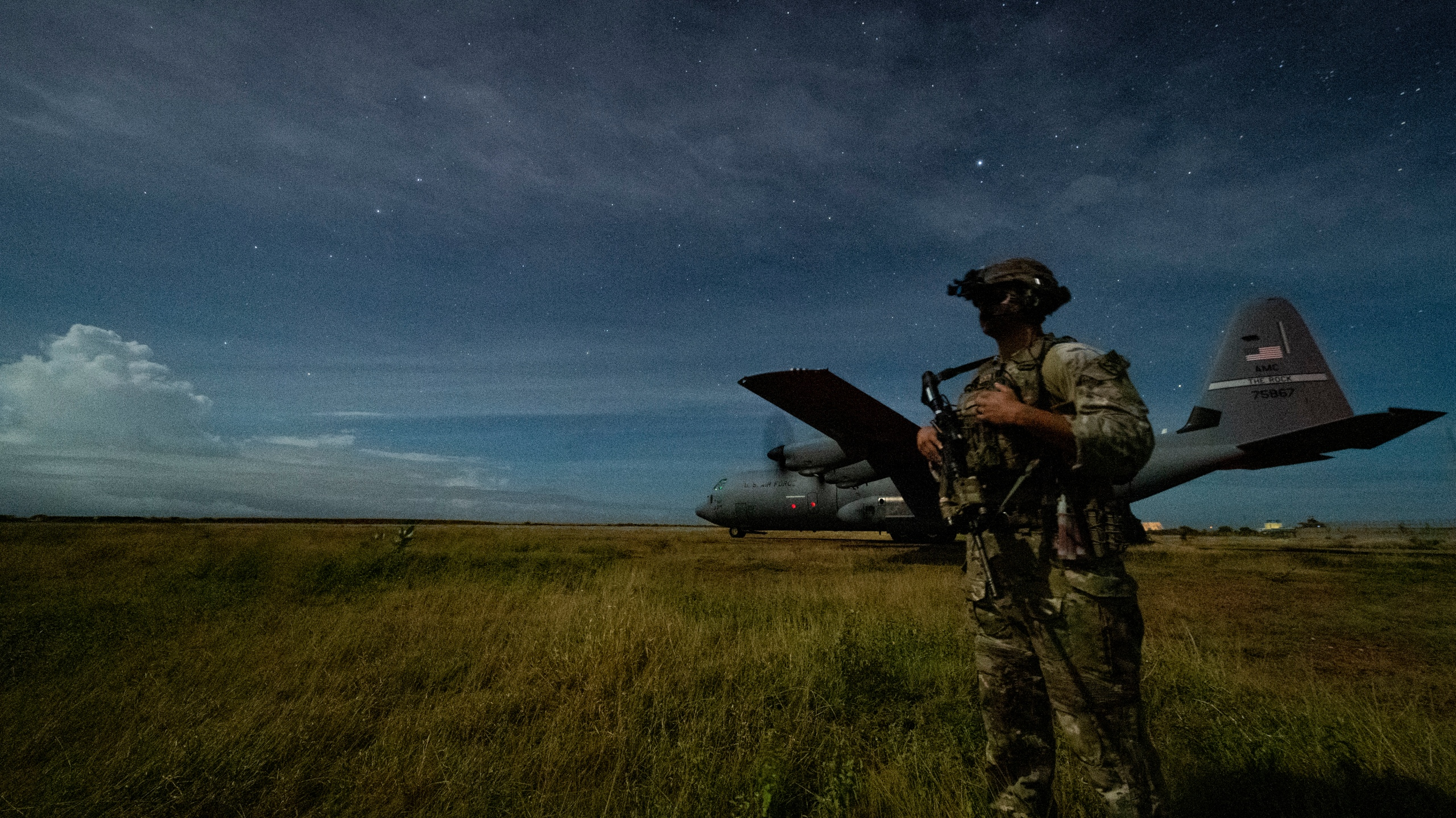 U.S. Army Spc. Kevin Martin, junior sniper, assigned to the 1-186th Infantry Battalion, Task Force Guardian, Combined Joint Task Force - Horn of Africa, provides security for a 75th Expeditionary Airlift Squadron (EAS) C-130J Super Hercules during unloading operations at an unidentified location in Somalia Sunday, June 28, 2020. (Tech. Sgt. Christopher Ruano/Combined Joint Task Force - Horn of Africa via AP)
