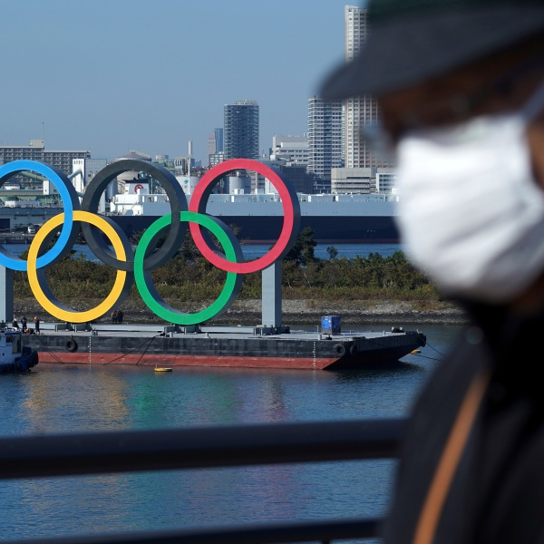 A man wearing a protective face mask to help curb the spread of the coronavirus walks with the Olympic rings in the background in the Odaiba section Tuesday, Dec. 1, 2020, in Tokyo. The rings were removed for maintenance four months ago shortly after the Tokyo Olympics were postponed until next year because of the COVID-19 pandemic. (AP Photo/Eugene Hoshiko)