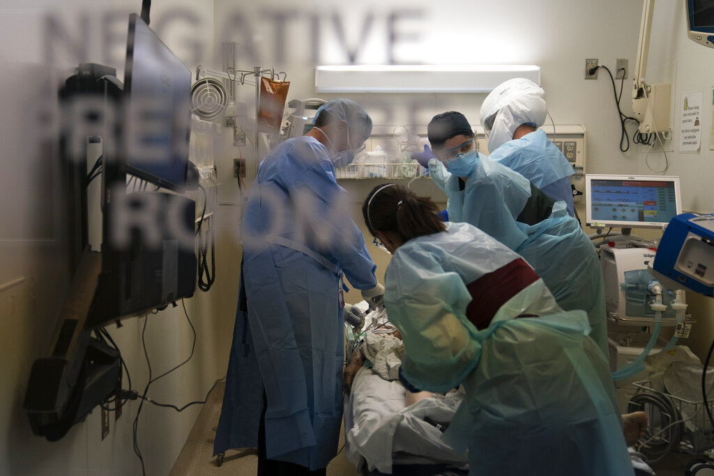 In this Nov. 19, 2020, file photo, EMT Giselle Dorgalli, second from right, looks at a monitor while performing chest compression on a patient who tested positive for coronavirus in the emergency room at Providence Holy Cross Medical Center in the Mission Hills section of Los Angeles. (AP Photo/Jae C. Hong, File)