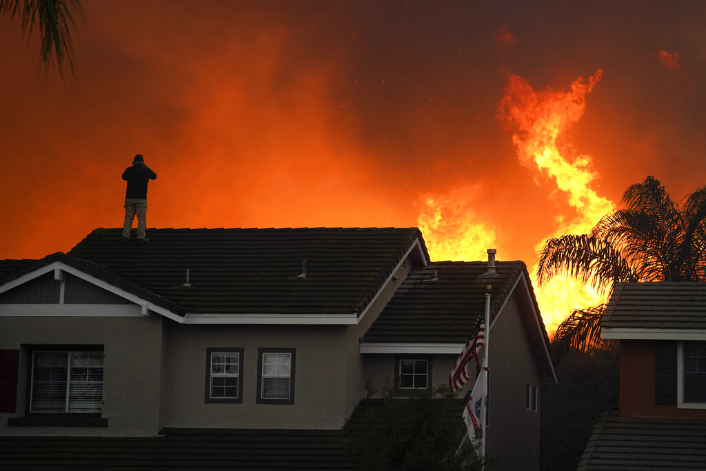 In this Tuesday, Oct. 27, 2020 file photo, Herman Termeer, 54, stands on the roof of his home as the Blue Ridge Fire burns along the hillside in Chino Hills, Calif. (AP Photo/Jae C. Hong)