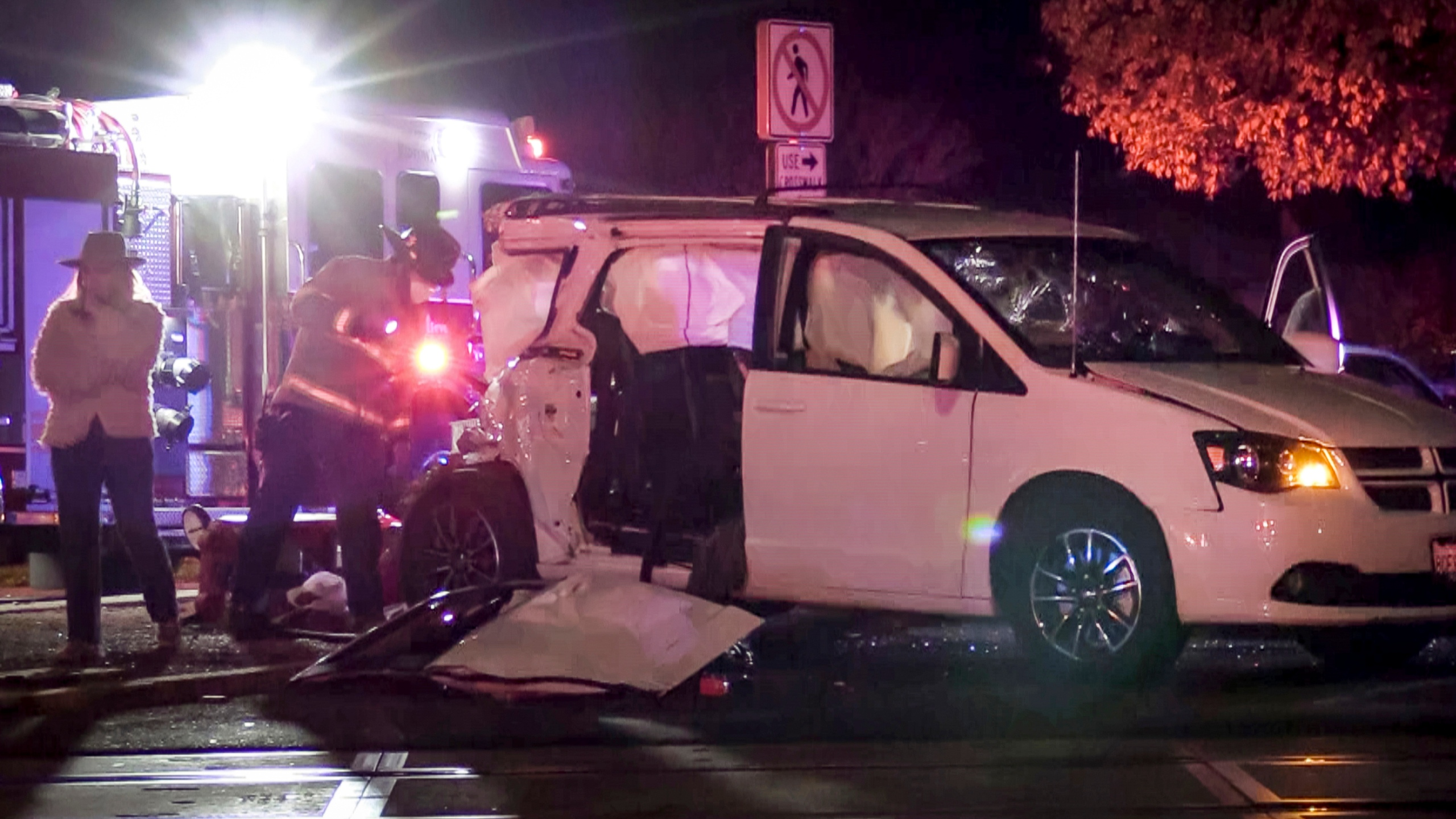 In this image from video, a firefighter inspects the scene where a small child was killed when a minivan was struck by a train while a family was waiting to enter a drive-thru Christmas lights display in Fresno, Calif., on Tuesday, Dec. 1, 2020. Police say the van with four people inside was stopped at an intersection when it was hit by an Amtrak train. (Craig Kohlruss/The Fresno Bee via AP)