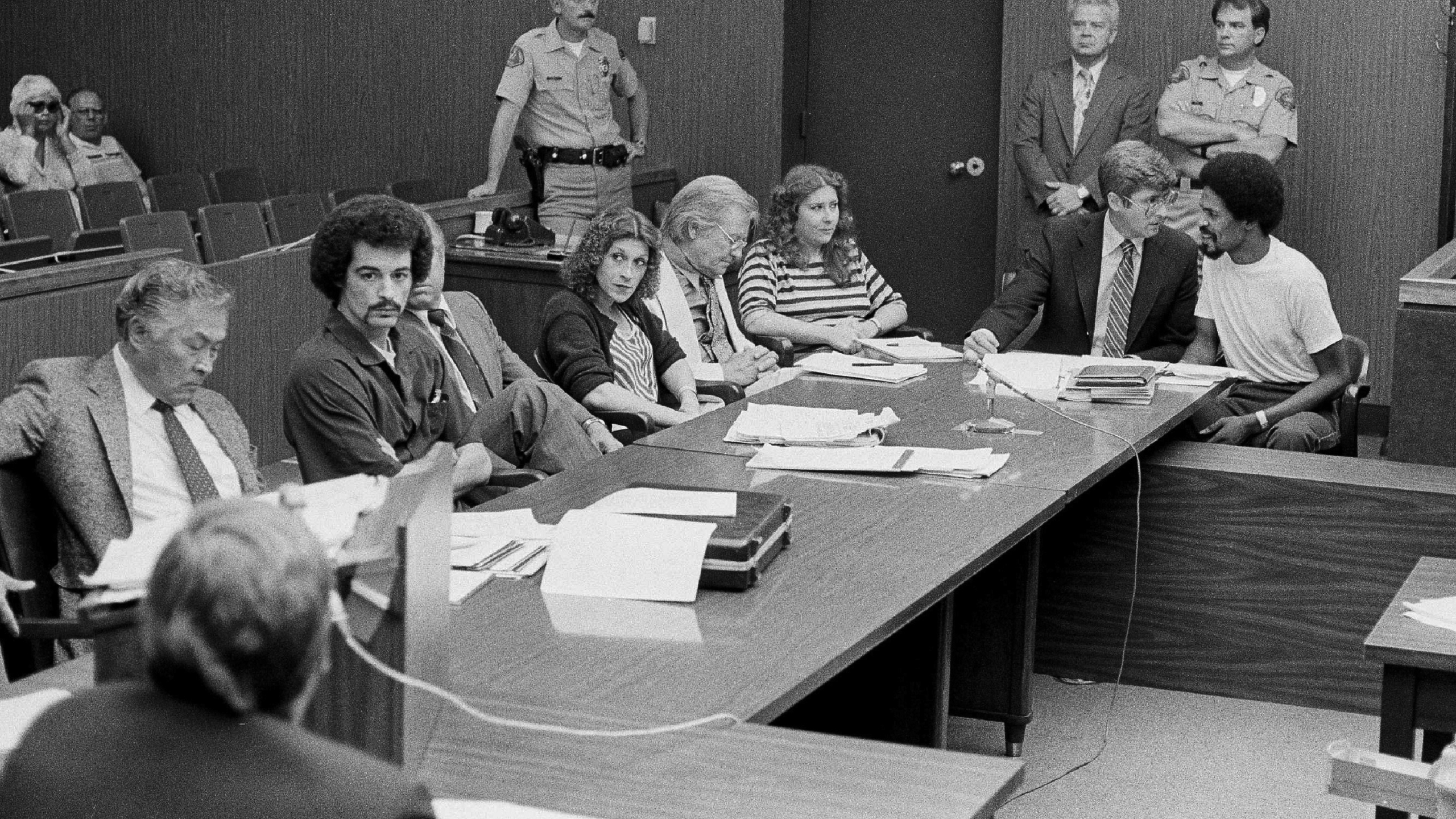 In this Aug. 22, 1983, file photo, four persons charged in connection with the June 2, 1983, fatal shooting of Los Angeles Police Officer Paul Verna sit with their attorneys during a preliminary hearing in a San Fernando, Calif., courtroom. Seated second from left to right, Kenneth Gay, an unidentified attorney, Robin Gay, attorney Elmer Docken, Pam Cummings, attorney Edward Rucker and Reynard Cummings. (AP Photo/Michael Tweed, File)