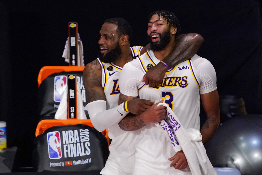Los Angeles Lakers' LeBron James, rear, and Anthony Davis (3) celebrate after the Lakers defeated the Miami Heat 106-93 in Game 6 of basketball's NBA Finals in Lake Buena Vista, Fla., in this Oct. 11, 2020, file photo. (AP Photo/Mark J. Terrill, File)