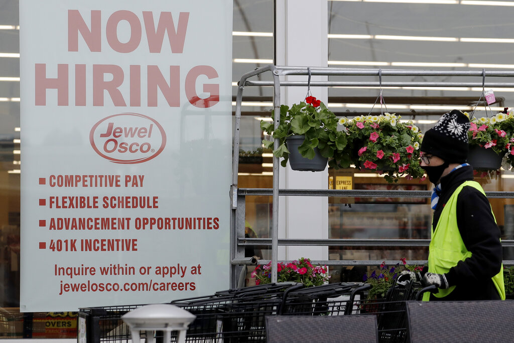 A man pushes carts as a hiring sign shows at a Jewel Osco grocery store in Deerfield, Ill., Thursday, April 23, 2020. (AP Photo/Nam Y. Huh)