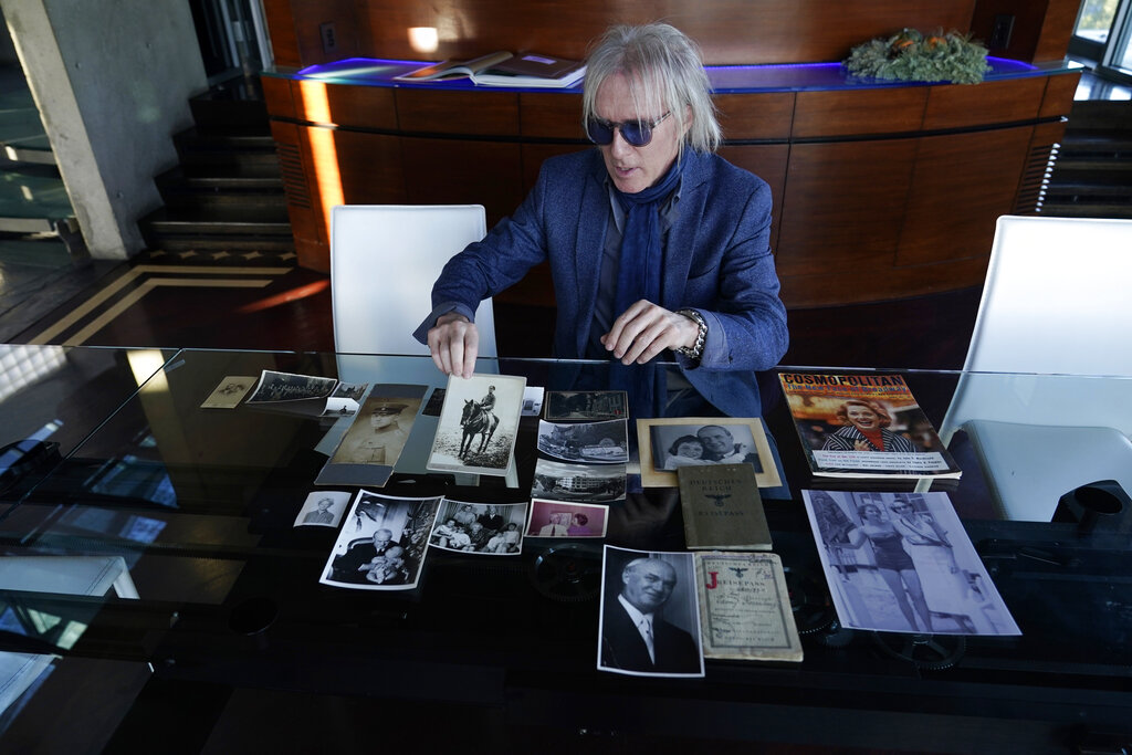 Jed Leiber shows photos of his grandfather Saemy Rosenberg's life at home, Dec. 3, 2020, in Los Angeles. (AP Photo/Marcio Jose Sanchez)