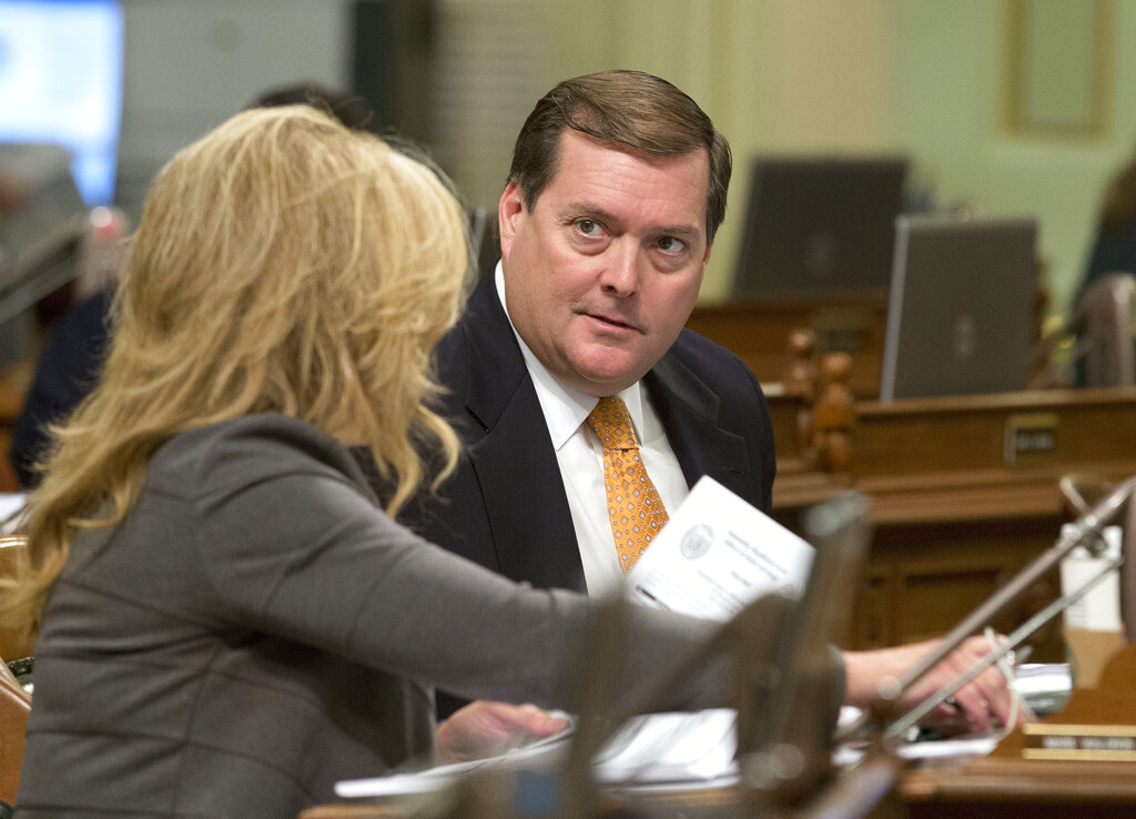 In this Aug. 30, 2016, file photo, Assemblyman Bill Brough, R-Dana Point, right, talks with Assemblywoman Marie Waldron, R-Escondido, in Sacramento, Calif. (AP Photo/Rich Pedroncelli, File)