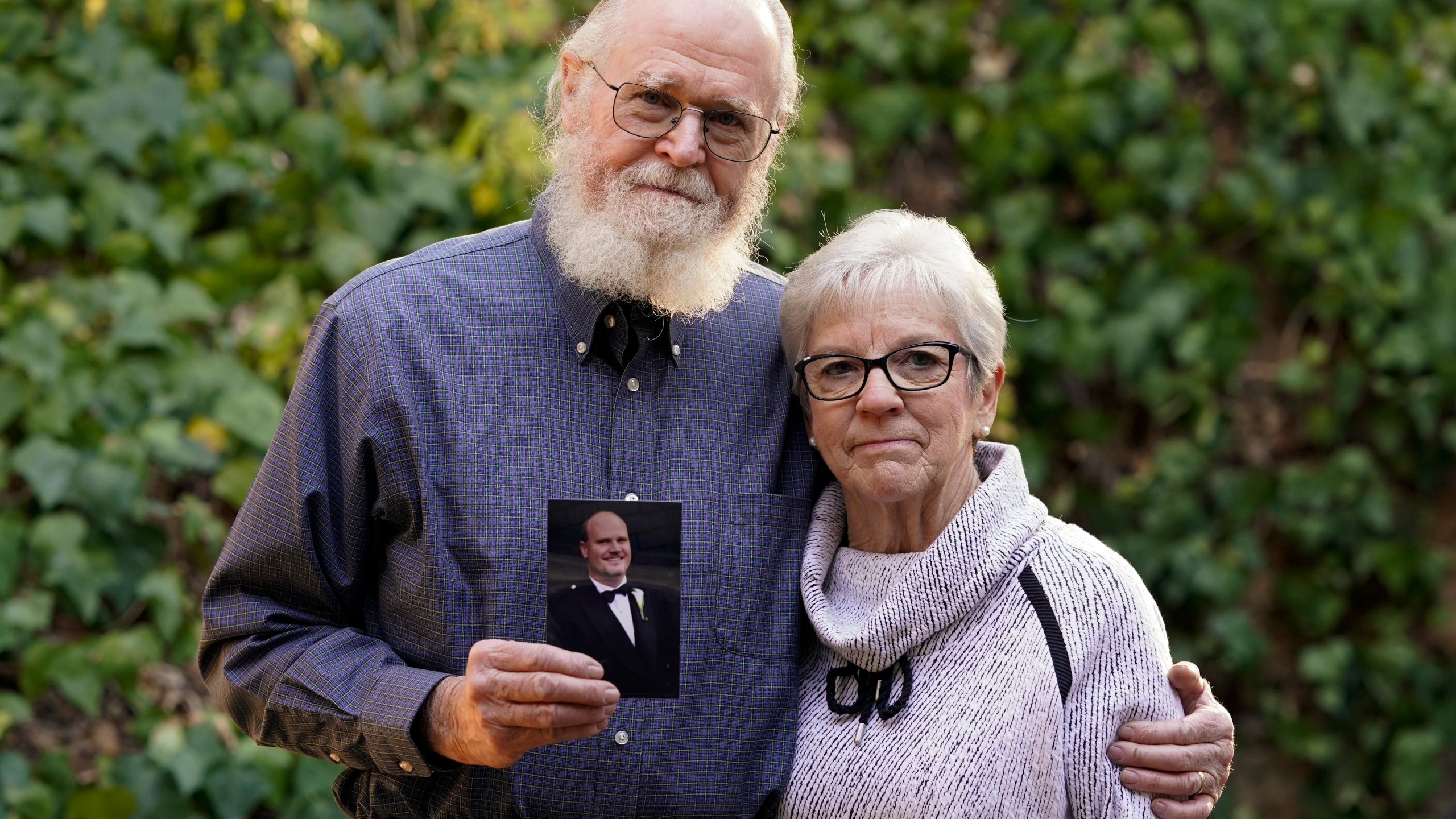 Clark McIlvain and Kathleen McIlvain hold a photo of their son, Charles McIlvain, at their home in Woodland Hills on Dec. 3, 2020. (Ashley Landis / Associated Press)