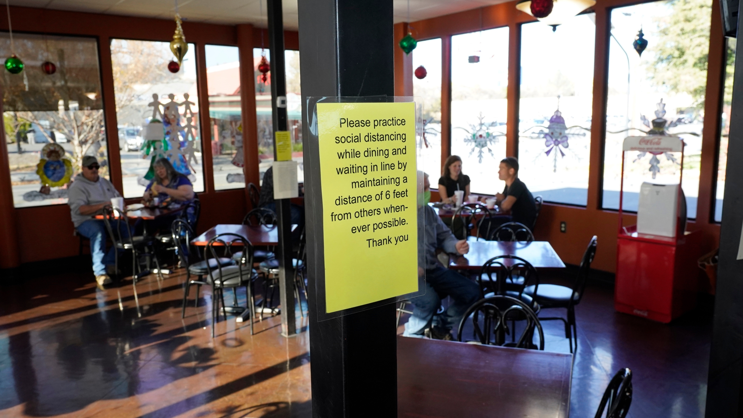 A sign advising patrons to maintain social distancing is posted in the indoor dining area of the San Francisco Deli in Redding, Calif., Thursday, Dec. 3, 2020. Brenda Luntey, who owns the deli with her husband, is openly violating the state's order to close her restaurant to indoor dining. She takes all the precautions advised, but doesn't force customers to wear a face mask. Luntey wants her customers and critics to know she is not a rule-breaker, and that it's a matter of survival. (AP Photo/Rich Pedroncelli)