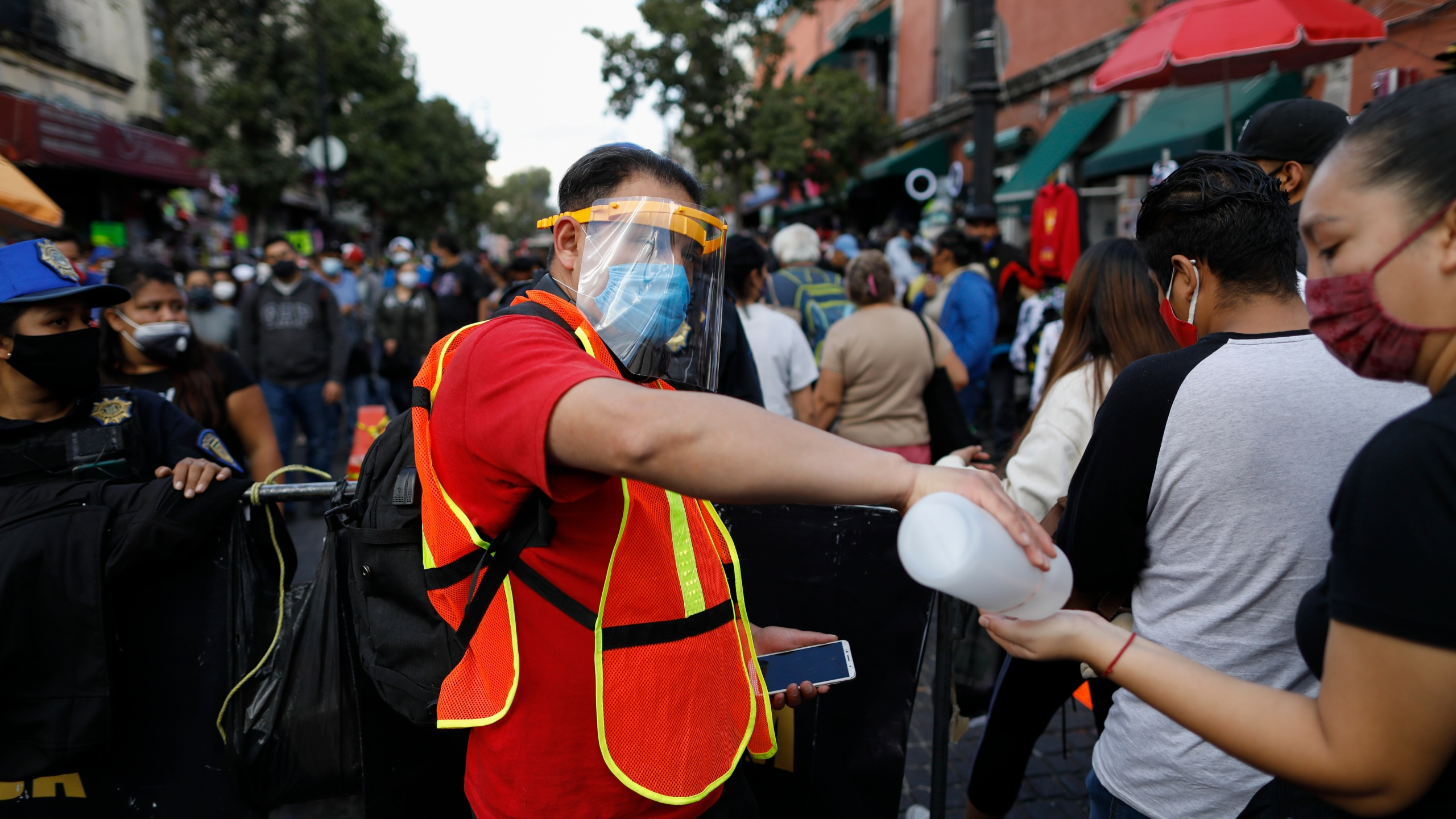 A city worker offers antibacterial gel to passing shoppers as they walk in a crowded commercial district of central Mexico City, Saturday, Dec. 5, 2020. (AP Photo/Rebecca Blackwell)