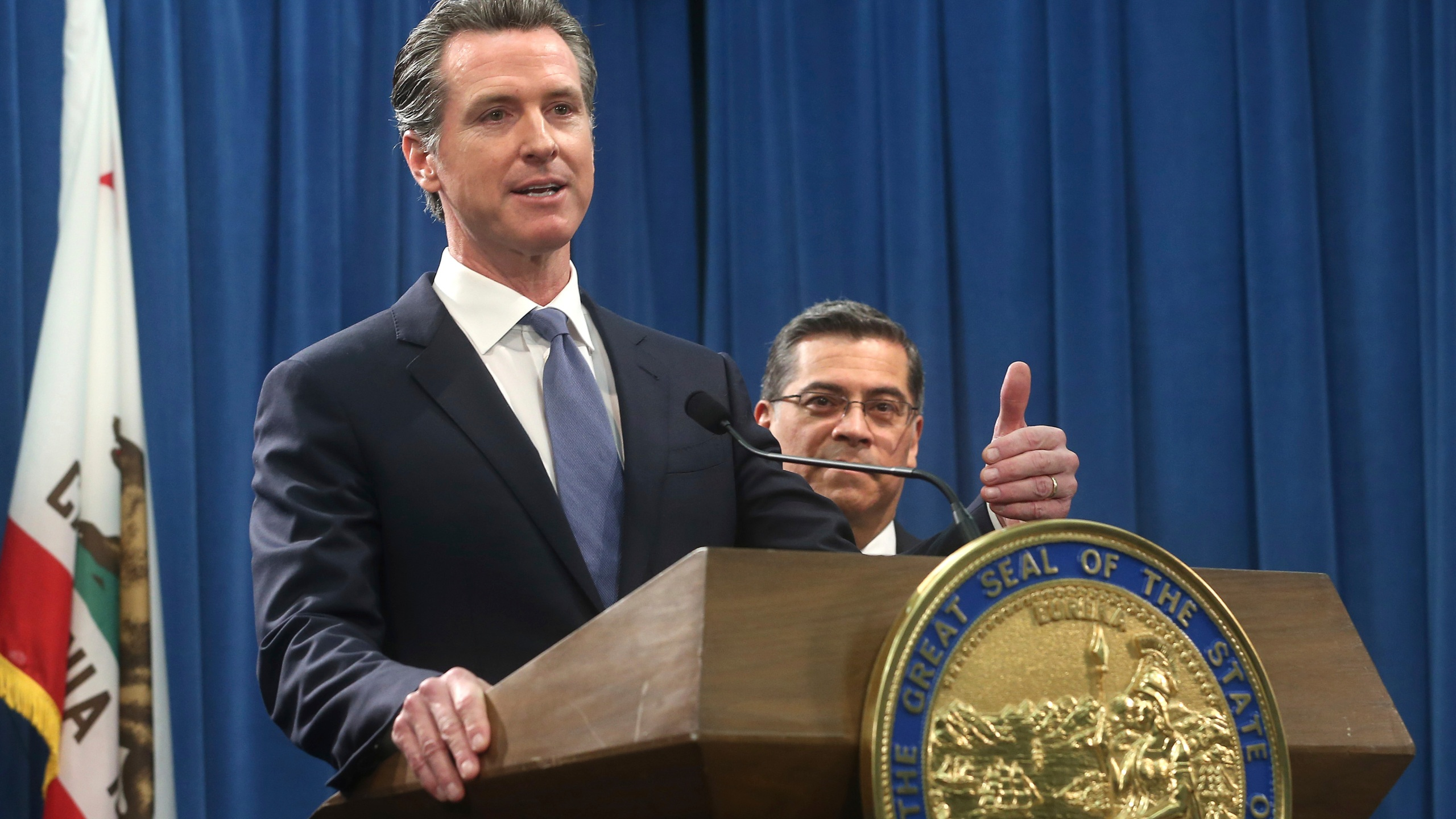 California Gov. Gavin Newsom, left, flanked by Attorney General Xavier Becerra, right, answers a question during a news conference in Sacramento on Feb. 15, 2019. (Rich Pedroncelli / Associated Press)