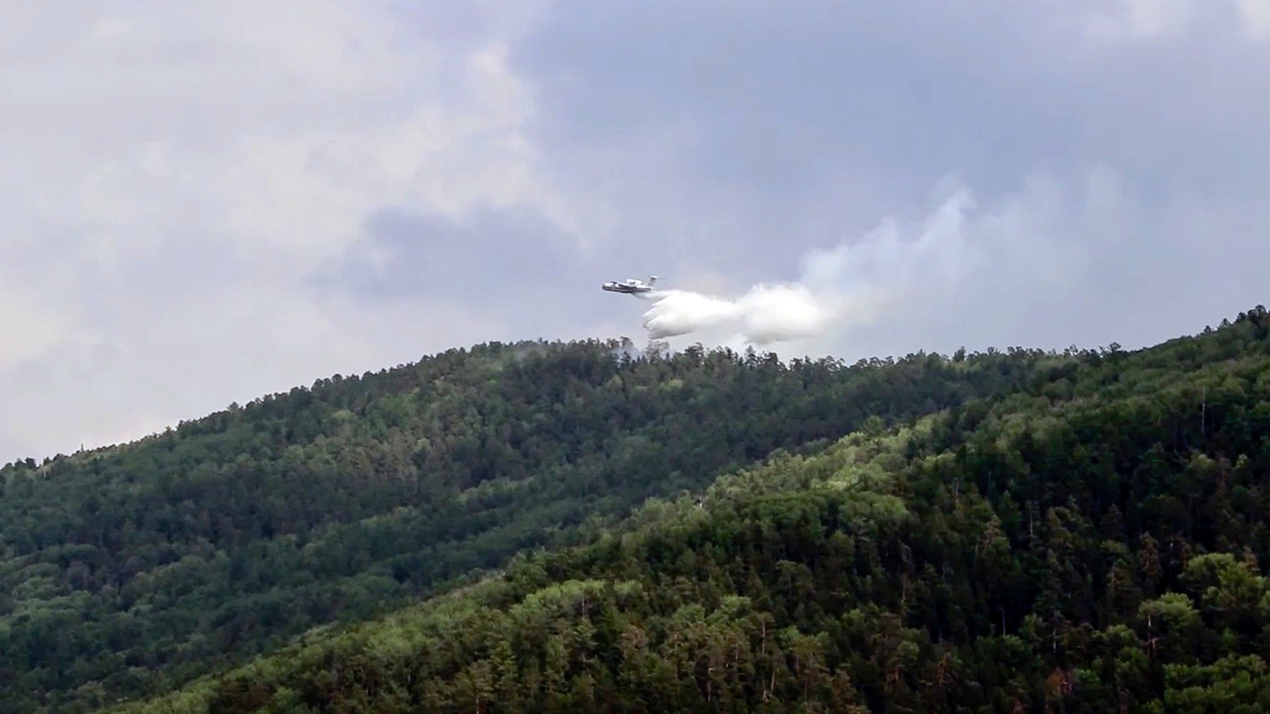 In this July 10, 2020, file image taken from video provided by Russian Emergency Ministry, a multipurpose amphibious aircraft releases water to extinguish a fire in the Trans-Baikal National Park in Buryatia, southern Siberia, Russia. The National Oceanic and Atmospheric Administration's annual Arctic Report Card, released on Tuesday, Dec. 8, 2020, shows how warming temperatures in the Arctic are transforming the region's geography and ecosystems. (Russian Emergency Ministry Press Service via AP, File)