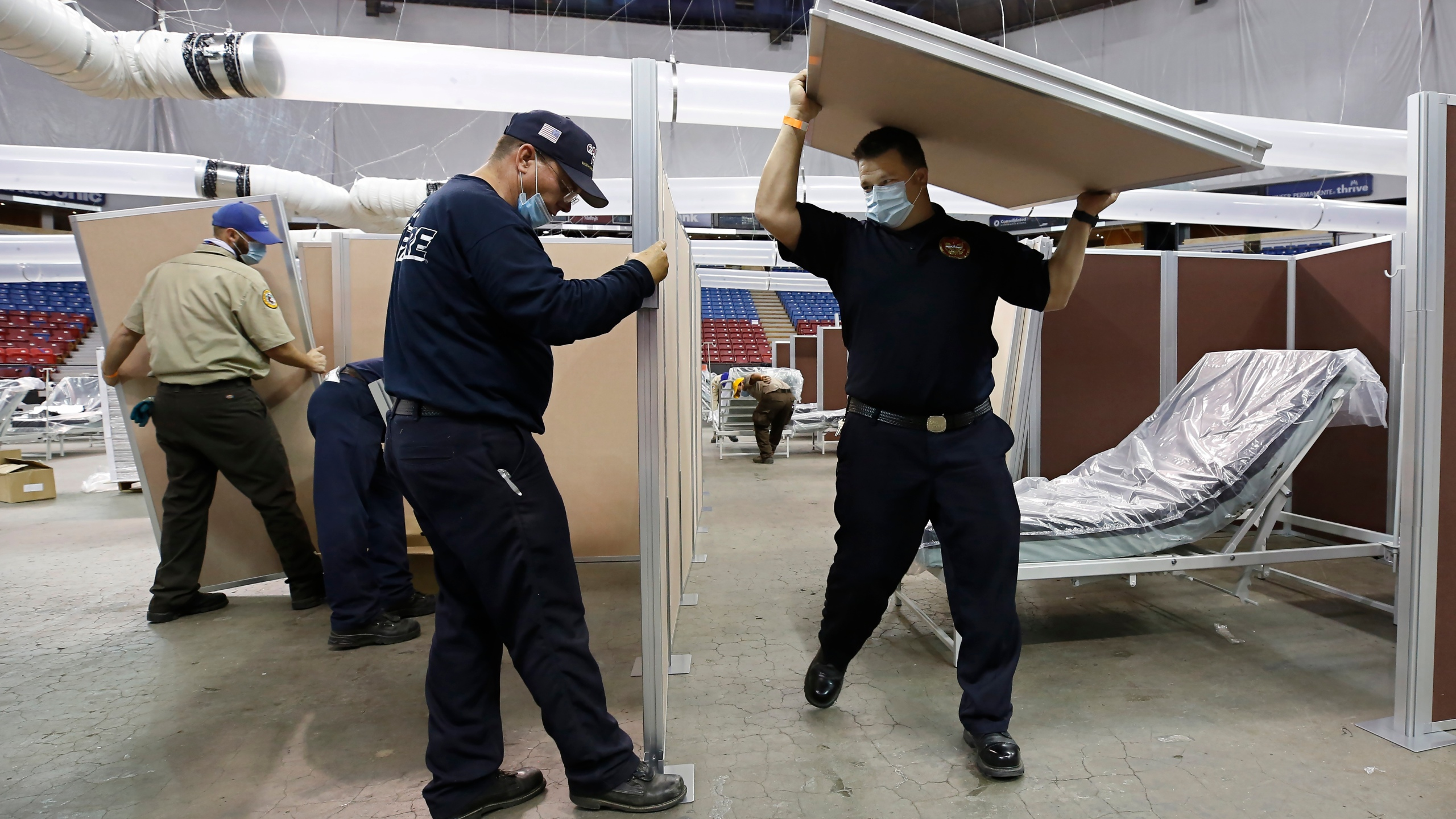 In this April 18, 2020, file photo, partitions are installed between beds as Sleep Train Arena is turned into a 400-bed emergency field hospital to help deal with the coronavirus, in Sacramento, Calif. Due to the recent spike in COVID-19 cases officials are rushing to reopen the former home of the NBA's Sacramento Kings, to patients. (AP Photo/Rich Pedroncelli, File)