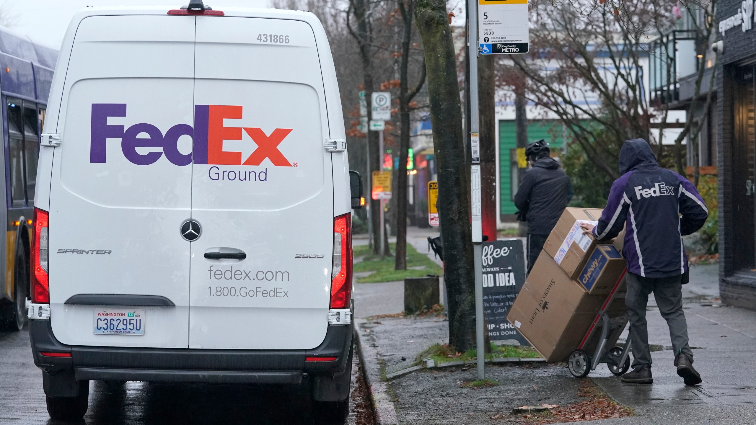 A driver with FedEx carries a package away from a van, Tuesday, Dec. 8, 2020, in Seattle. Store are warning online shoppers that if holiday purchases aren't made soon, they may not be delivered in time for Christmas. (Ted S. Warren/Associated Press)