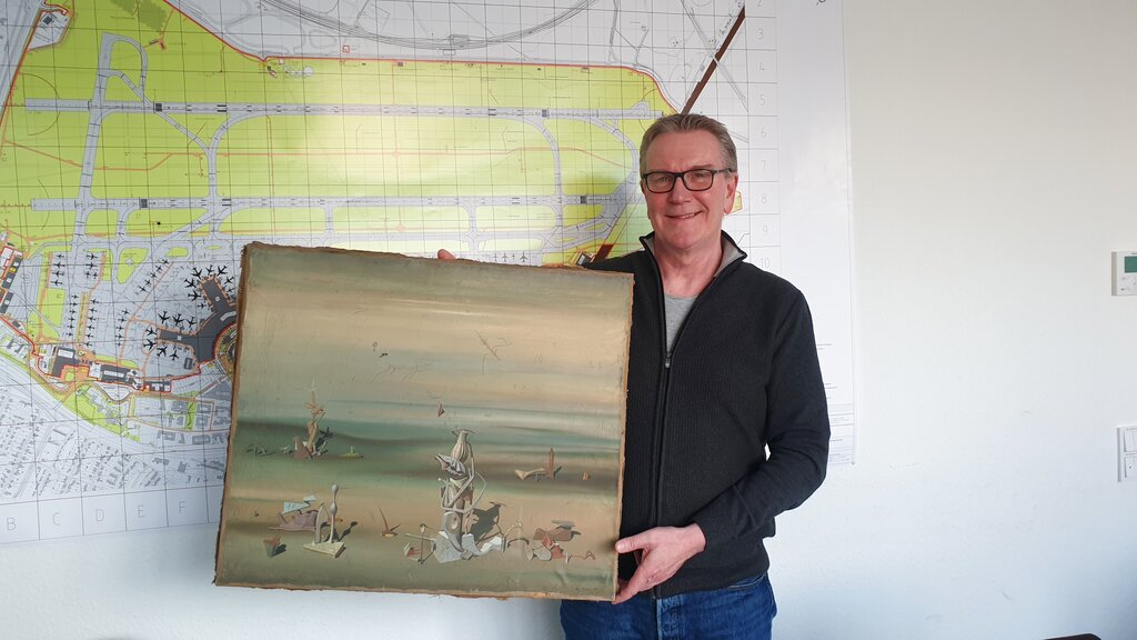 In this photo released by the police department in Duesseldorf on Thursday Dec. 10, 2020, showing Chief Detective Michael Dietz holding a painting from French artist Yves Tanguy. (Polizei Duesseldorf via AP)