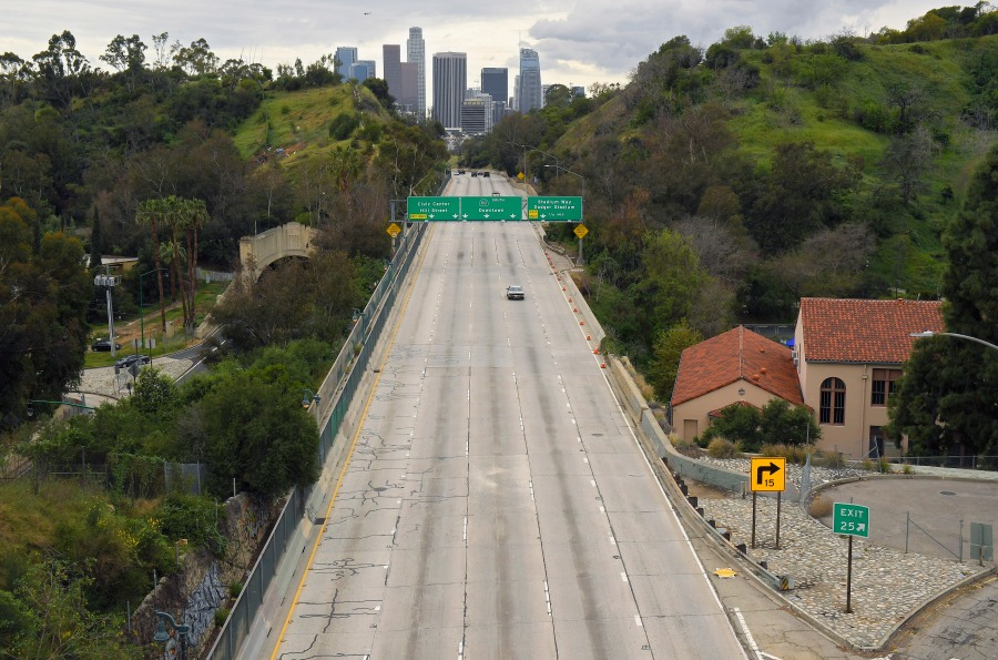 In this Friday, March 20, 2020 file photo, extremely light traffic moves along the 110 Harbor Freeway toward downtown Los Angeles in the mid-afternoon. Traffic would normally be bumper-to-bumper during this time of day on a Friday. New calculations released on Thursday, Dec. 10, 2020, show the world's carbon dioxide emissions plunged 7% in 2020 because of the pandemic lockdowns. (AP Photo/Mark J. Terrill)