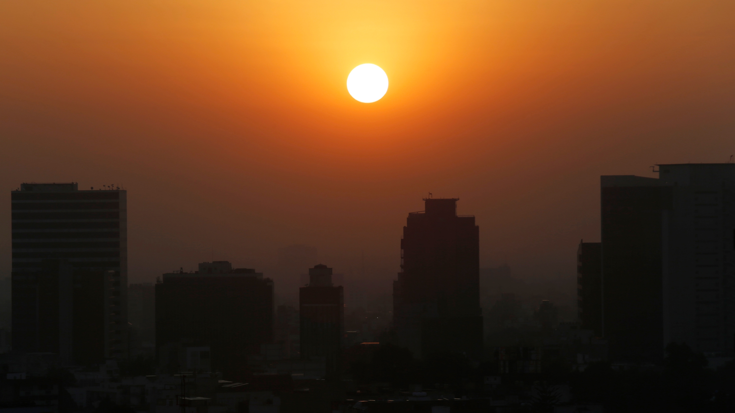 In this Thursday, Feb. 20, 2020 file photo, the sun rises amid smog during the dry season in Mexico City. Five years after a historic climate deal in Paris, world leaders are again meeting to increase their efforts to fight global warming. (AP Photo/Marco Ugarte)