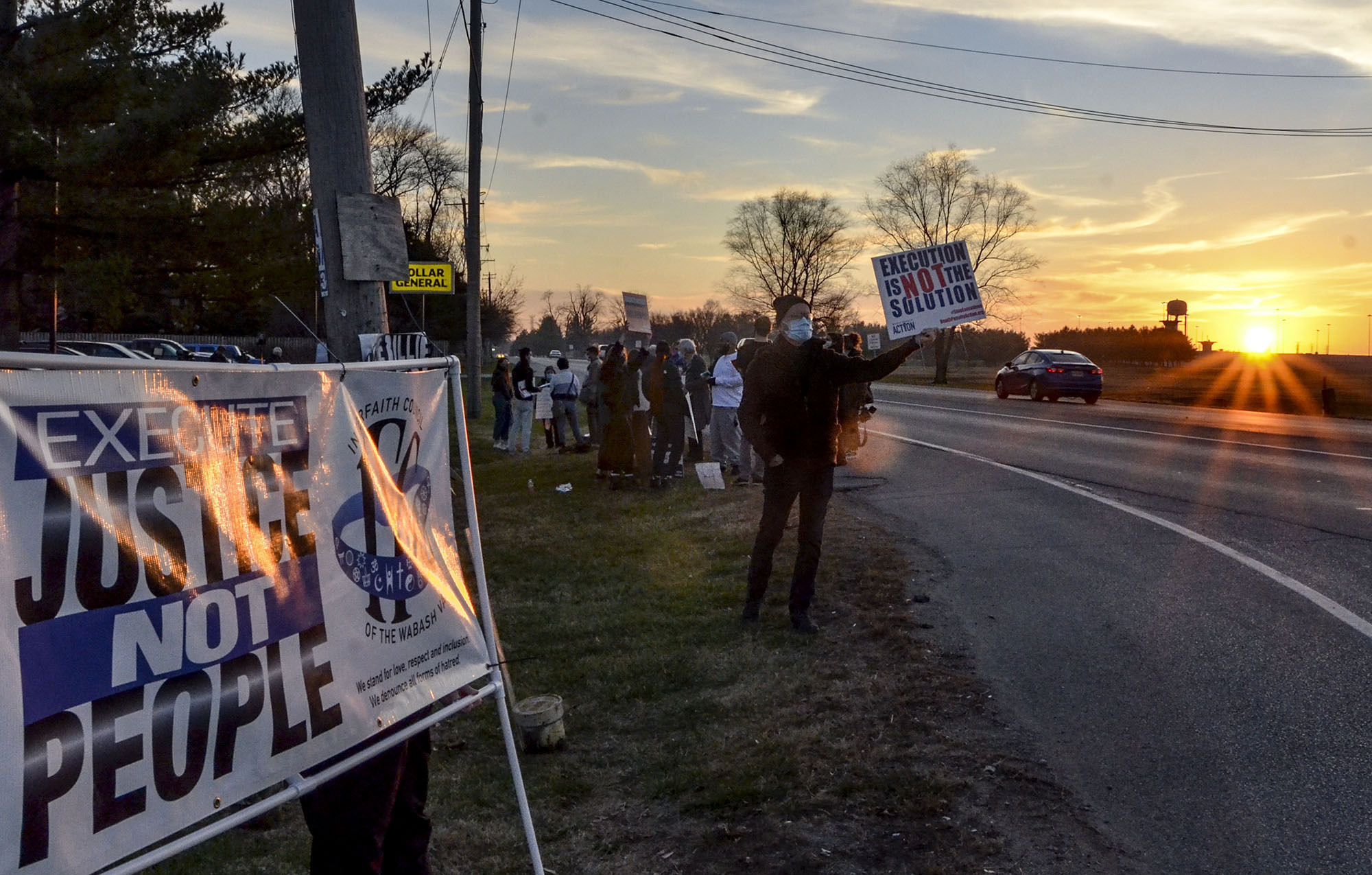 Protesters line Prairieton Road across from the Federal Death Chamber in Terre Haute, Ind., during a protest against the execution of Brandon Bernard on Thursday evening, Dec. 10, 2020. (Austen Leake/The Tribune-Star via AP)