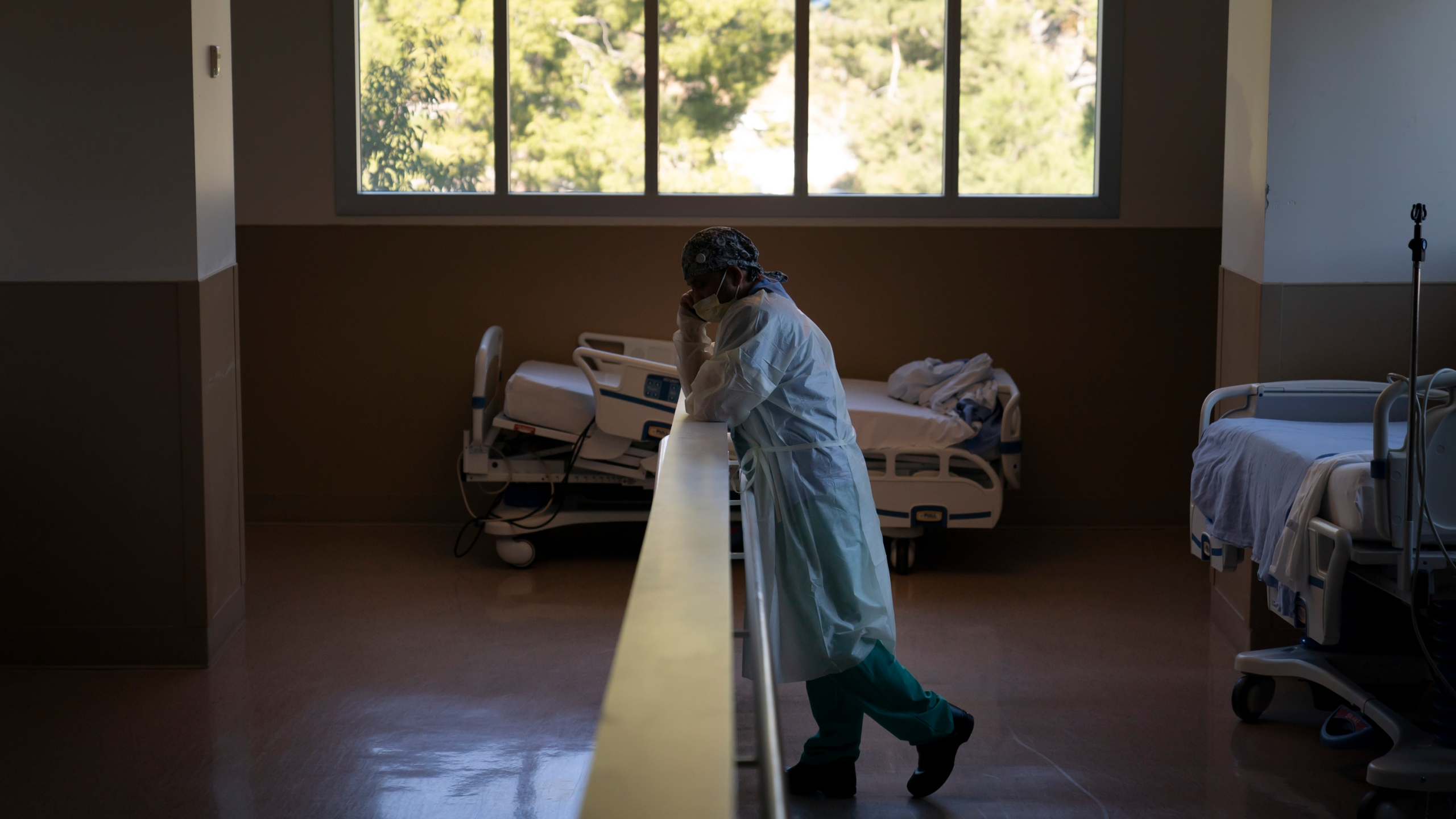 In this Nov. 19, 2020, file photo, respiratory therapist Babu Paramban talks on the phone next to hospital beds while taking a break in the COVID-19 unit at Providence Holy Cross Medical Center in the Mission Hills section of Los Angeles. (Jae C. Hong/AP Photo)