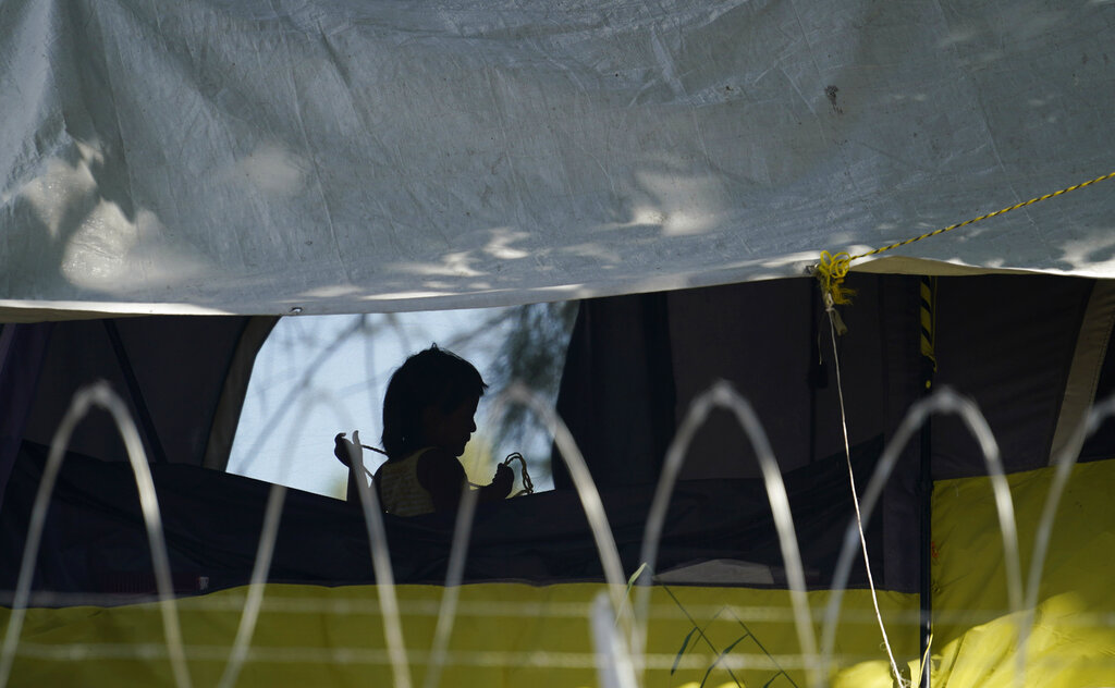 In this Nov. 18, 2020, file photo, a young girl plays in her family's tent at a camp of asylum seekers stuck at America's doorstep, in Matamoros, Mexico. Increasing numbers of parents and children are crossing the border, driven by violence and poverty in Central America and growing desperation in migrant camps in Mexico. U.S. Customs and Border Protection said Monday, Dec. 14, 2020 that it made 4,592 apprehensions of unaccompanied immigrant children in November, more than six times the figure in April. (AP Photo/Eric Gay File)