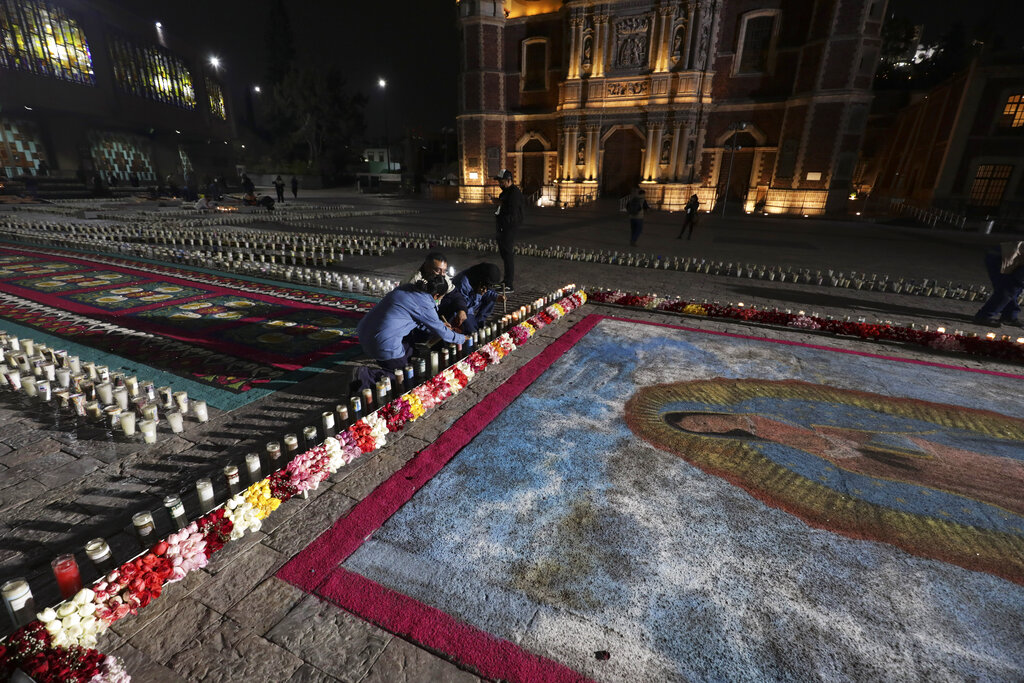 People lights a candlenext to an image the Virgin of Guadalupe outside the Basilica of Guadalupe in Mexico City, Friday, Dec. 11, 2020. (AP Photo/Eduardo Verdugo)
