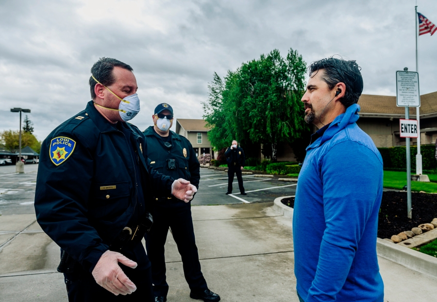 In this April 5, 2020, file photo, Lodi Police Capt. Sierra Brucia, left, meets with Pastor Jon Duncan of the Cross Culture Christian Center on Palm Sunday in Lodi, Calif. The church sued Gov. Gavin Newsom arguing his stay-at-home order violated their constitutional rights. In San Joaquin County, part of California's vast Central Valley that produces most of the country's fruits and vegetables, the coronavirus is the leading cause of death this year and things will only worsen as infections skyrocket and hospitals fill beyond capacity. Like most of California, the city of Lodi is under a broad shutdown order as Christmas approaches, and its residents and businesses are grappling with how to stay safe while keeping their economy operating. (Daniel Kim/The Sacramento Bee via AP)