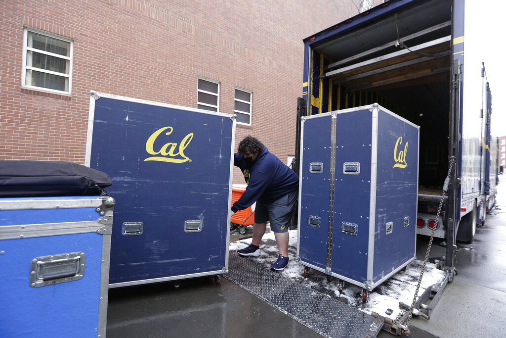 California equipment truck driver Dustin Sandoval loads equipment for his team into the trailer outside Martin Stadium after the NCAA college football game between Washington State and California was canceled on Dec. 12, 2020, in Pullman, Wash. (AP Photo/Young Kwak)