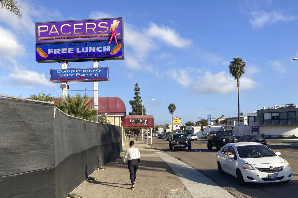 In this Dec. 10, 2020, file photo, a person walks past Pacers Showgirls International in San Diego. San Diego County has suspended enforcement of COVID-19 restrictions on restaurants and live entertainment establishments after a local judge found in favor of two strip clubs that defied a state shutdown order and indicated the ruling applied more broadly. (AP Photo/Elliot Spagat, File)