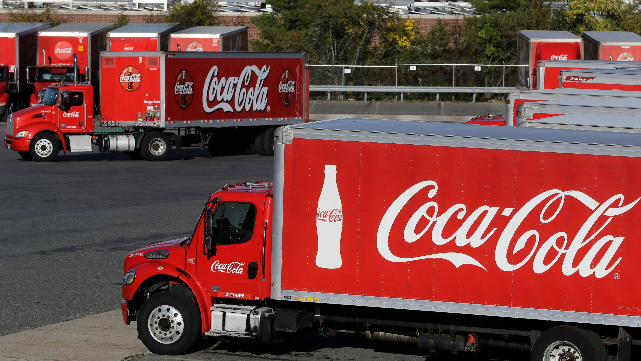 In this Oct. 14, 2019, photo a truck with the Coca-Cola logo, behind left, maneuvers in a parking lot at a bottling plant in Needham, Mass. (AP Photo/Steven Senne, File)