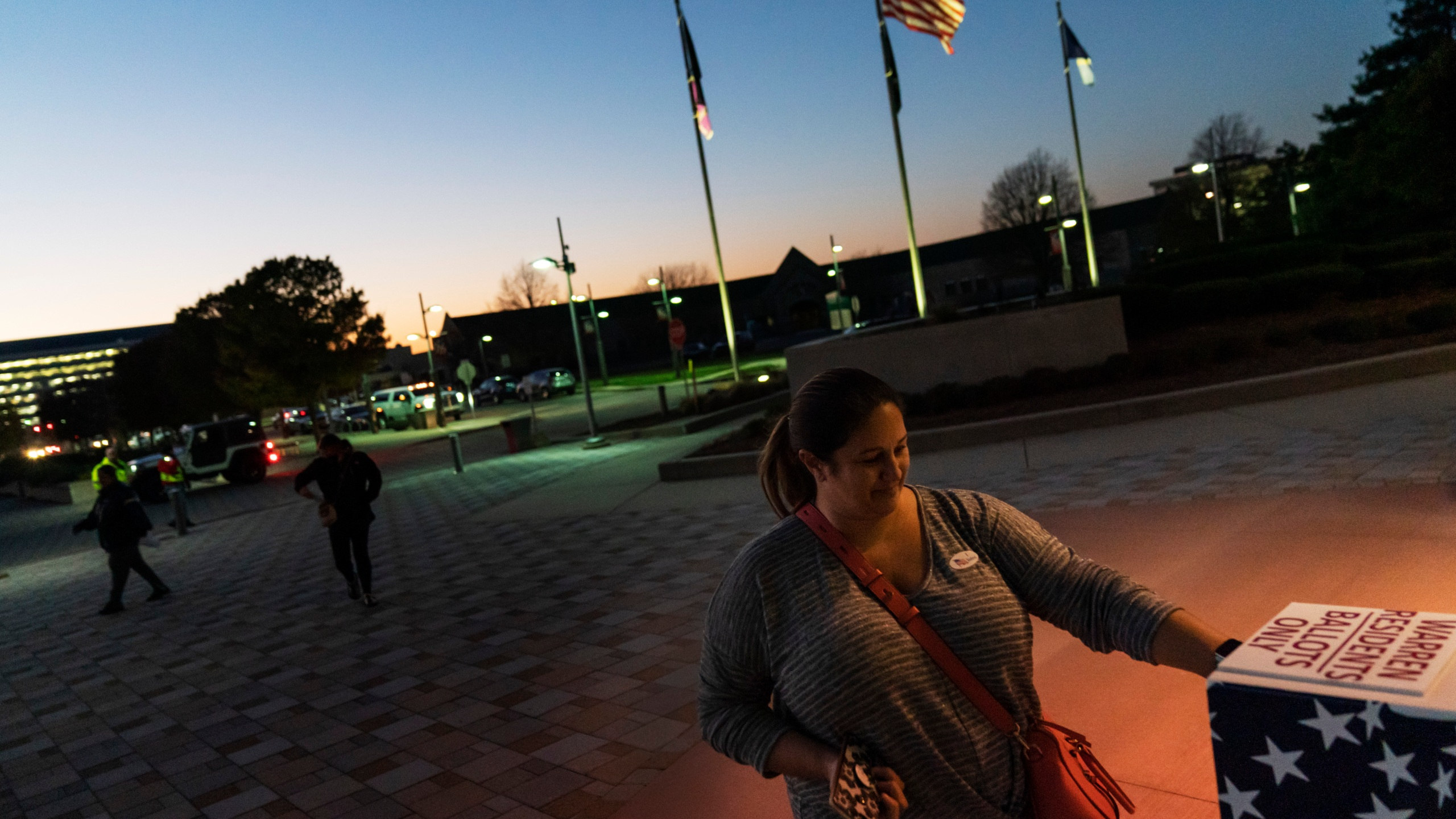 In this Tuesday, Nov. 3, 2020 file photo, Wendy Gill inserts her absentee ballot at a drop-off box as the sun sets on Election Day outside City Hall in Warren, Mich. (David Goldman/AP Photo)