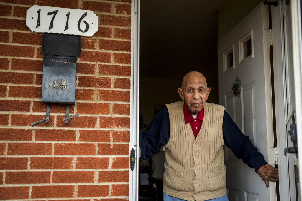 In this Wednesday, Dec. 9, 2020, file photo, Alfred Farrar, a Tuskegee Airman who is celebrating his 100th birthday in December, poses for a portrait in the doorway of his home in Lynchburg, Va. (Kendall Warner/The News & Advance via AP, File)
