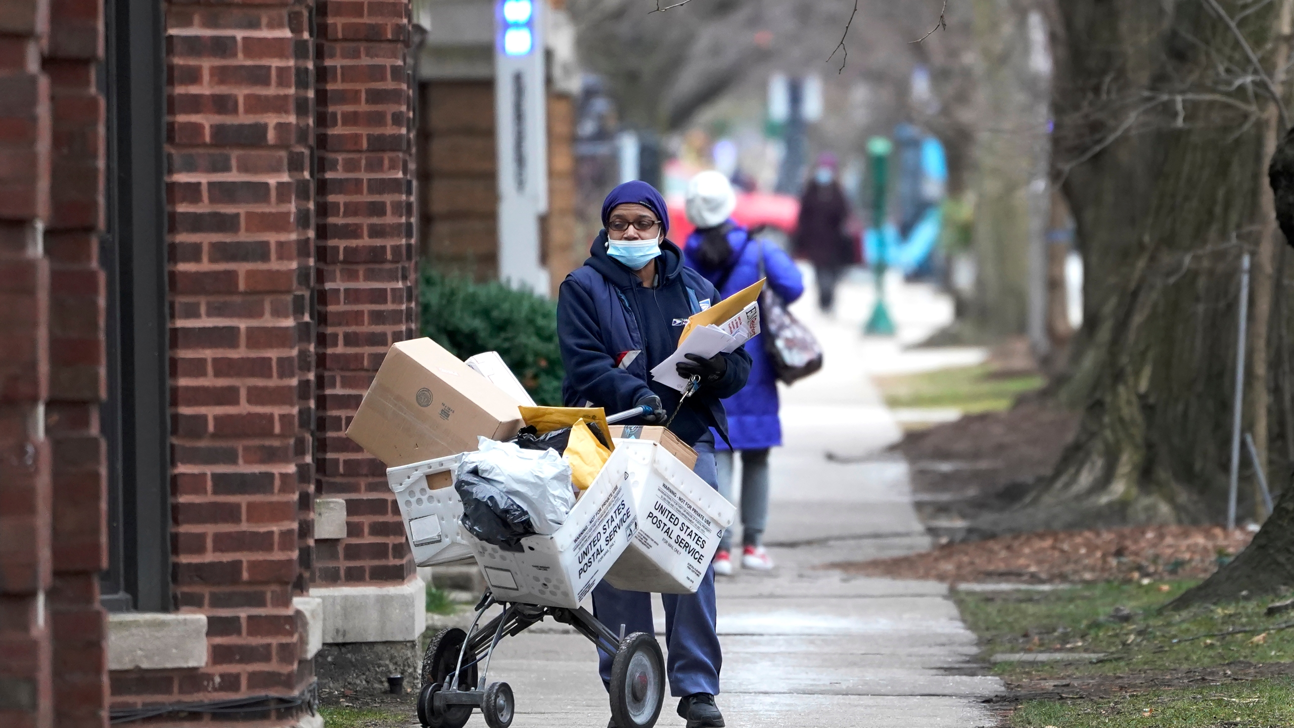 A U.S. postal worker delivers packages, boxes and letters Dec. 22, 2020, along her route in the Hyde Park neighborhood of Chicago on Dec. 22, 2020. (Charles Rex Arbogast)