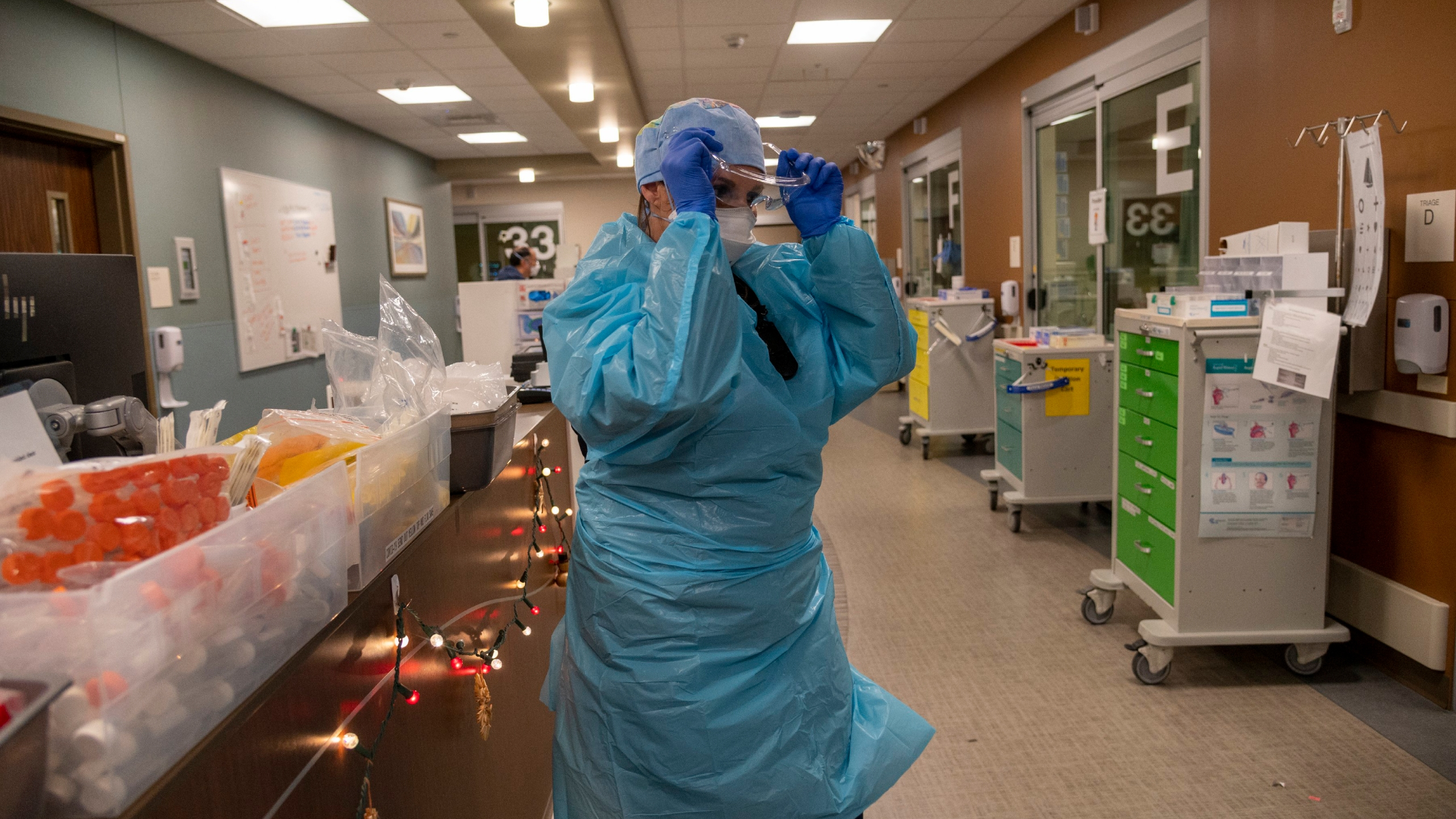 Registered Nurse Allison Shiftar puts on protective glasses as she gets ready to go into one of the triage rooms to care for a COVID-19 positive patient in the emergency department at Sutter Roseville Medical Center in Roseville, Calif. on Dec. 22, 2020. (Renee C. Byer/The Sacramento Bee via AP, Pool)