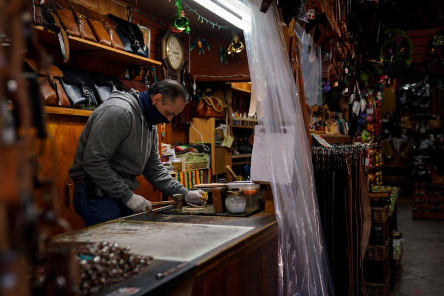 Leather artisan Armando Murillo works in his shop on Olvera Street in downtown Los Angeles, Wednesday, Dec. 16, 2020. Olvera Street, known as the birthplace of Los Angeles, has been particularly hard hit by the coronavirus pandemic, with shops and restaurants closed and others barely hanging on. Only a handful of businesses remain open on weekdays as tourism has cratered and downtown offices are closed and festive events held throughout the year have been canceled. (Jae C. Hong / Associated Press)