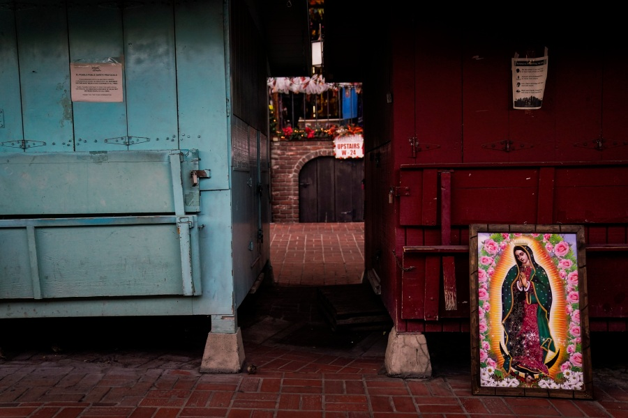 A framed painting depicting Our Lady of Guadalupe is propped against a shuttered market stall on empty Olvera Street in downtown Los Angeles, Wednesday, Dec. 16, 2020. Olvera Street, known as the birthplace of Los Angeles, has been particularly hard hit by the coronavirus pandemic, with shops and restaurants closed and others barely hanging on. (Jae C. Hong / Associated Press)