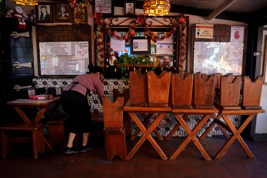 "Debbie Briano, a fourth-generation owner of Mexican restaurant, El Rancho Grande, works in her restaurant next to chairs and tables pushed against the wall on Olvera Street in downtown Los Angeles, Wednesday, Dec. 16, 2020. Briano still decorated her cafe like she normally would at Christmas. She bought poinsettias, put up a real tree, hung tinsel, lights, and strung little snowmen and Santa Claus above her window. ""I had to do that to feel normal,"" she said. ""I' m not going to let COVID take away our Christmas magic."" (Jae C. Hong / Associated Press)"