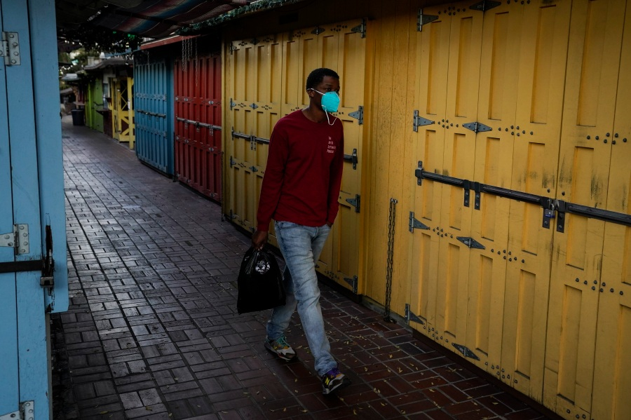 A man wearing a face mask walks past shuttered market stalls on empty Olvera Street in downtown Los Angeles, Tuesday, Dec. 15, 2020. The tree-covered brick alley typically teeming with tourists is empty. Many of the shops that sell everything from traditional Mexican folk dresses to paintings of artist Frida Kahlo to sombreros are padlocked and the ones open have few, if any, customers. (Jae C. Hong / Associated Press)