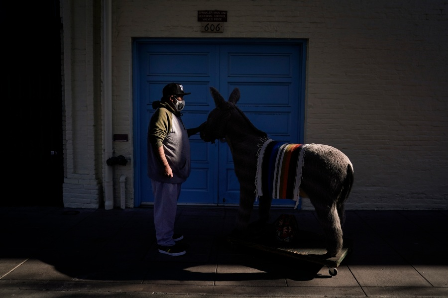 Jesus Hernandez, a merchant who owns a gift shop on Olvera Street that only opens on weekends due to the pandemic, waits for a key to store his uncle's life-size stuffed donkey, a photo prop named George, in downtown Los Angeles, Wednesday, Dec. 16, 2020. Olvera Street, known as the birthplace of Los Angeles, has been particularly hard hit by the coronavirus pandemic, with shops and restaurants closed and others barely hanging on. (Jae C. Hong / Associated Press)